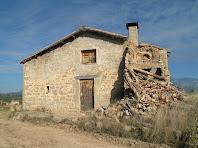 La façana principal de la masia de Montoliu amb la part del pou enrunada