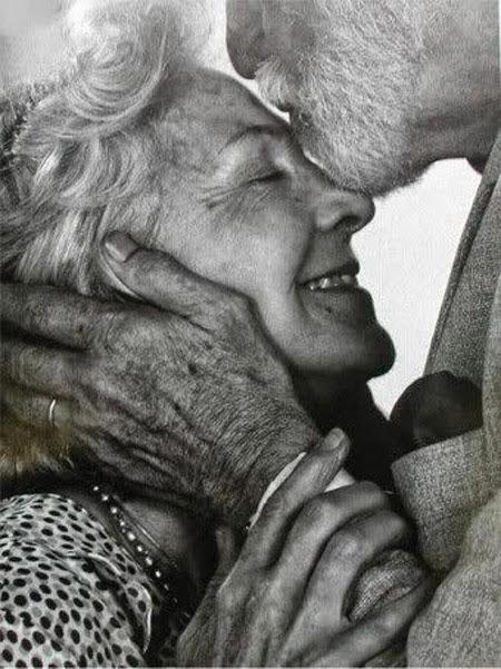 целует в лоб свою жену