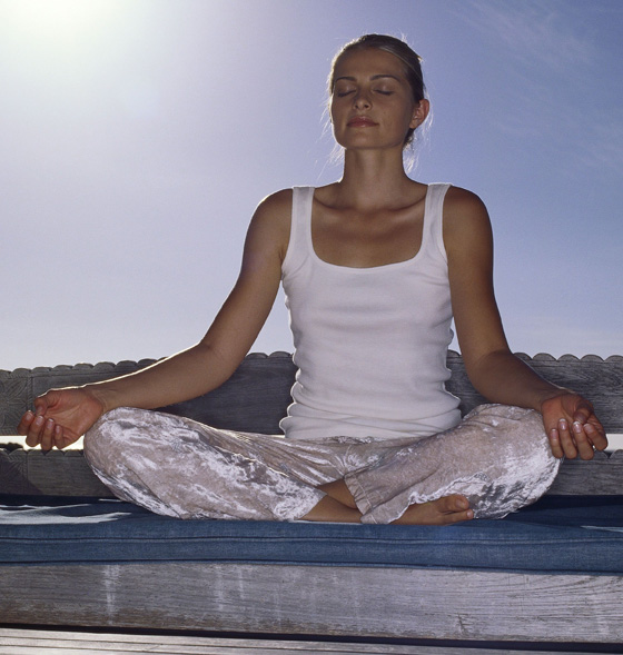 Young woman practicing yoga on a bench outdoors