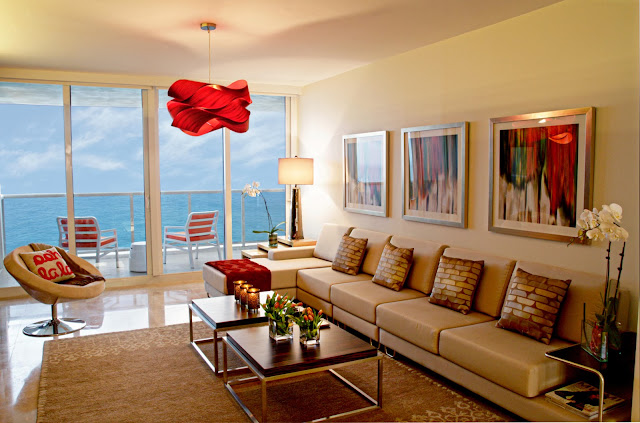 lively living room scheme with pops of red and greens and also having the benefit of direct access to the balcony for the ocean view