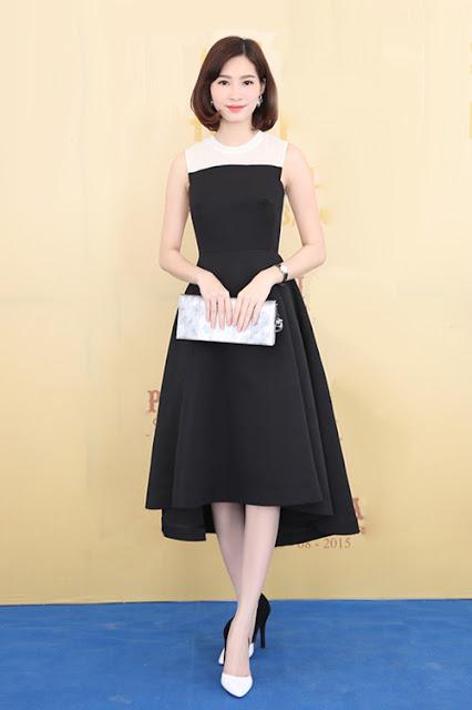 Hoa hậu Đặng Thu Thảo chọn phong cách nữ tính với váy trắng đen phom cổ điển. Người đẹp không kết hợp phụ kiện rườm rà. Đôi giày hai gam màu đen trắng giúp người đẹp thêm phần cuốn hút.