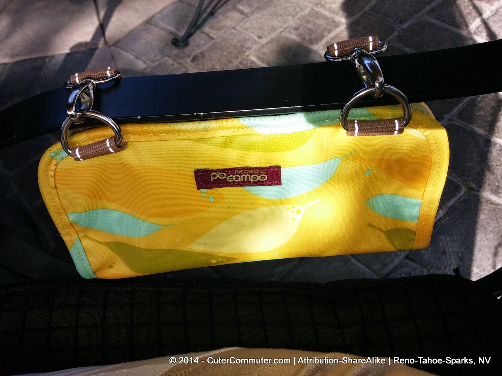 Po Campo Yellow Feathers Six Corners Handlebar Bag strapped on arm of patio chair
