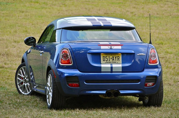 Rear view of blue 2012 Mini John Cooper Works Cooper Coupe with silver top in country setting