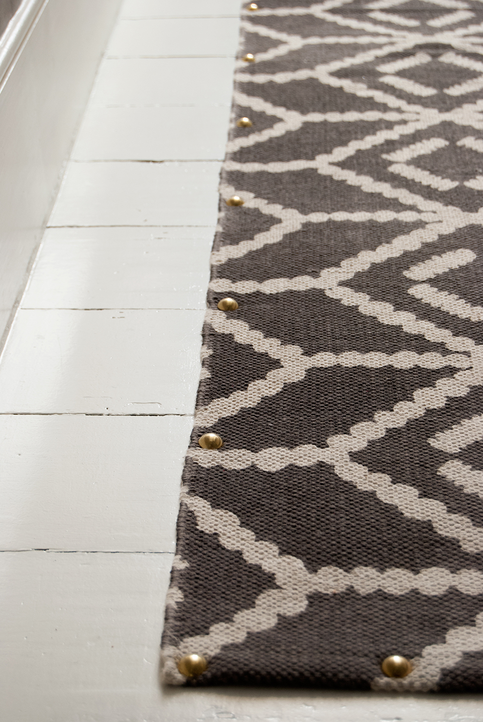 Close up of rug runner with brass studs and white painted floorboards