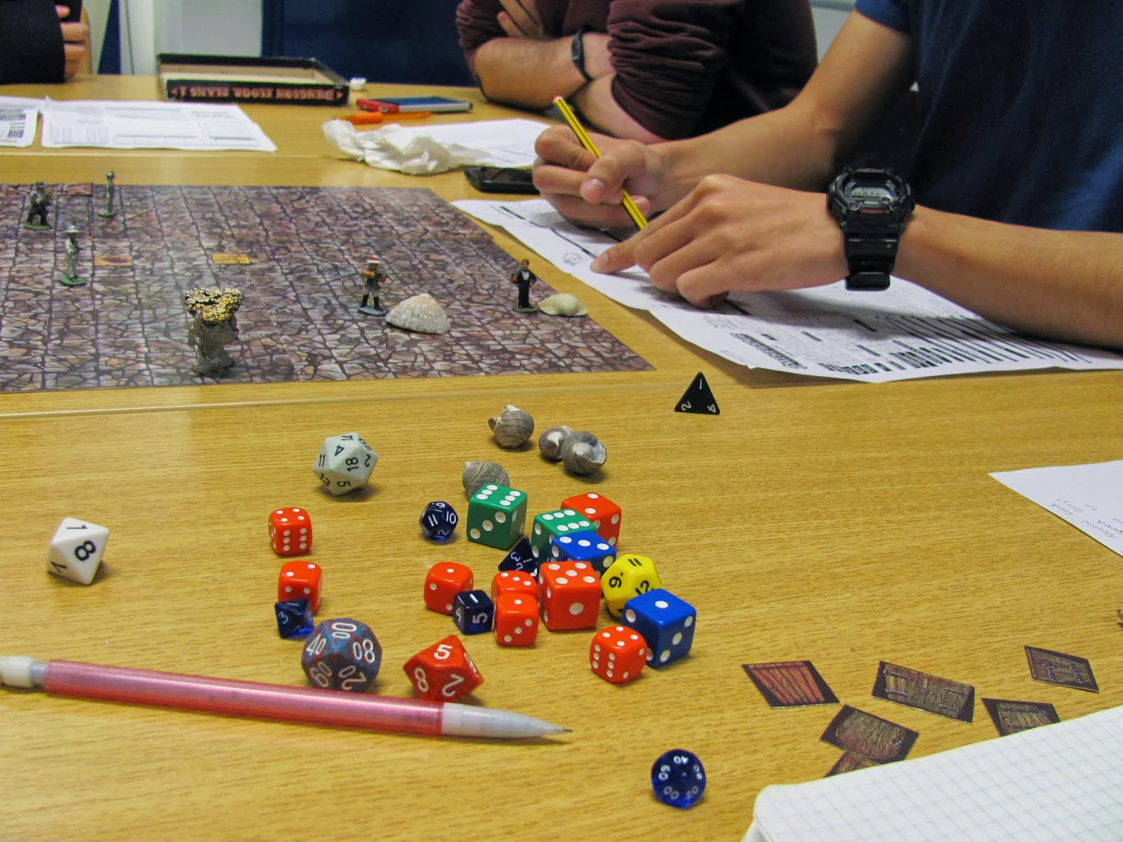 Dice and character sheets are seen with a battle map game board playing Pathfinder RPG