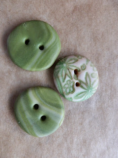 Three green and cream Polymer clay buttons, one with printed design and two marble effect.