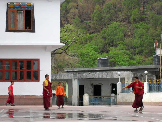 Монахи играют в бадминтон во дворе монастыря