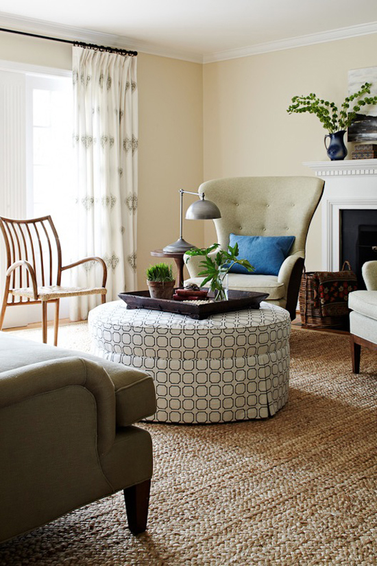 A round ottoman unifies the various seating furniture in this living room designed by Lauren Liess.