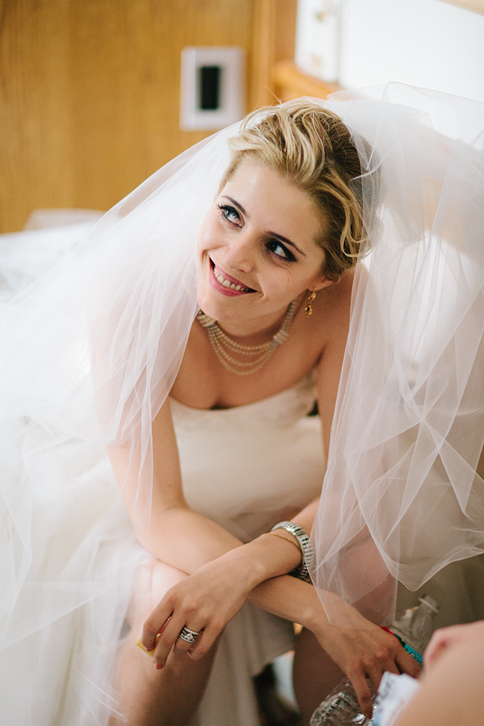 Adorable bride wearing Monique Lhuillier eating a snack photo by STUDIO 1208