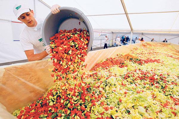 SEORANG sukarelawan menambahkan kandungan sayur-sayuran sebagai usaha untuk menghasilkan salad terbesar di dunia di Pantelimon semalam.