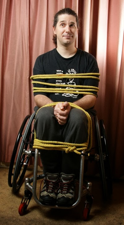 Man in a manual wheelchair, tied to the chair with many ropes ... satirical