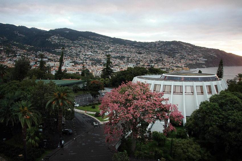 Fotografia da cidade, ao fundo, sobre a encosta e o Casino e Jardins do Hotel Pestana em primeiro plano