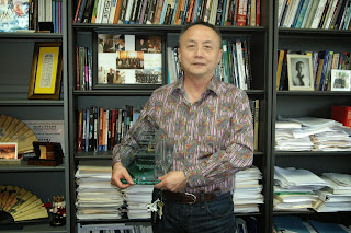 Dr. Solomon Zhao holds his Distinguished Alumni Award from Washington State University.