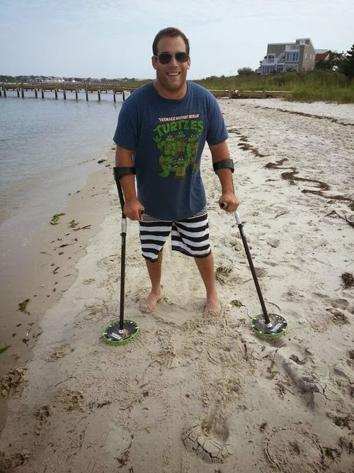 Young man standing with two forearm crutches on sandy beach