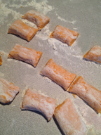 """Sweet potato gnocchi being cut from dough """"ropes"""""""