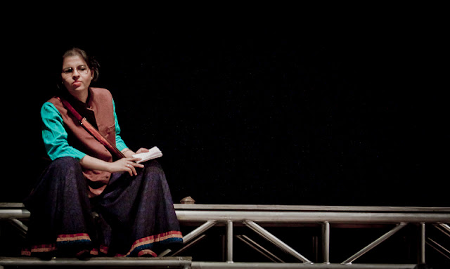 The narrator with her impeccable prononciation carried the play with ease and dignity. The stage was set clearly with the ramp where she is sitting currently acting as the railway station, balcony, and street.