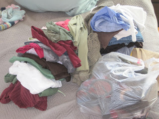 Pile of sweaters, tops, pants, and trash bag full of shoes