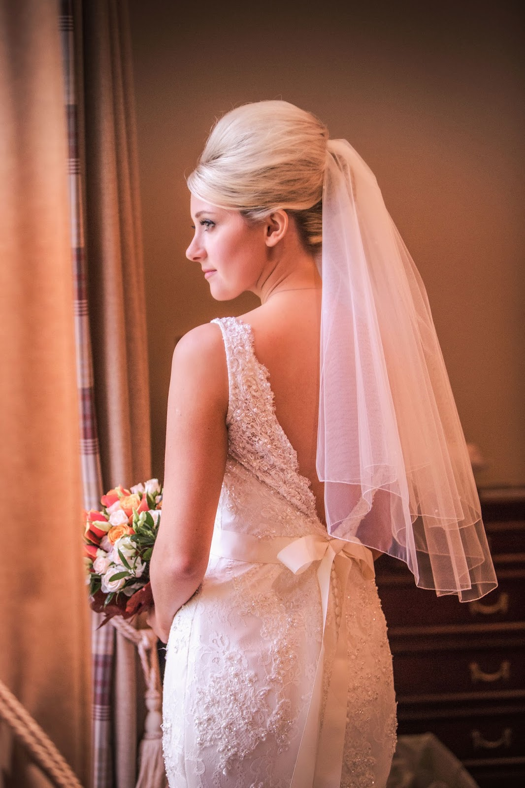 bride wears her hair up in a french roll style with volume accessorised by a soft veil