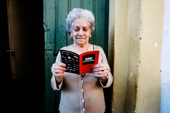 Una señora del El Puerto de Santa María lee la agenda del festival