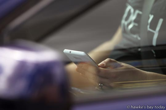 A woman driver looks at her cellphone while stopped at the traffic lights on the corner of St Aubyn St East and Karamu Rd North, Hastings, for a story about texting and using a cellphone, mobile phone while driving. photograph