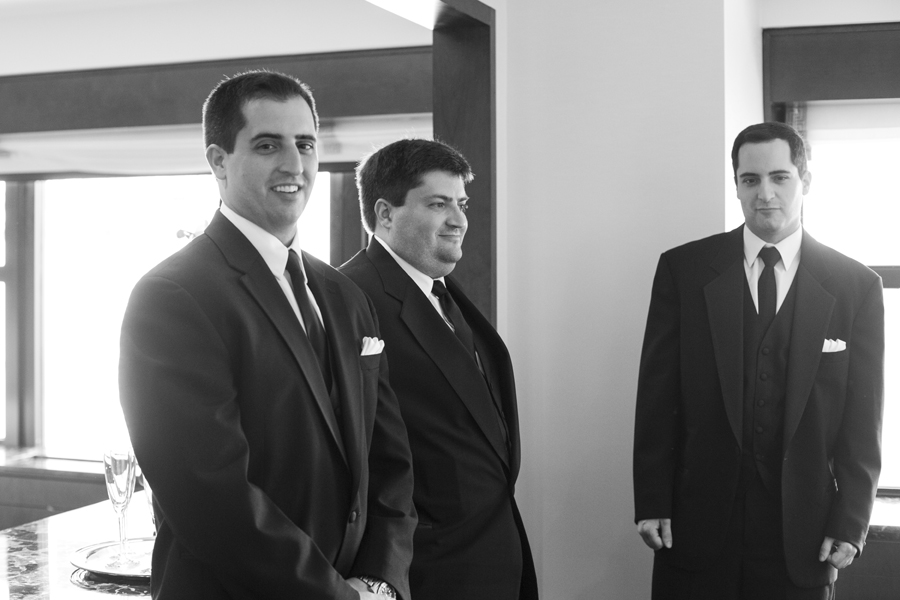 black and white of candid smiling groom with brother
