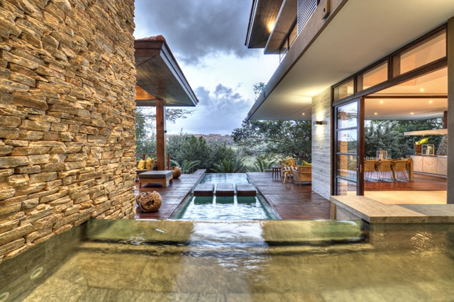 View of the pool and a small waterfall into the pool in the Contemporary South African SGNW House by Metropole Architects