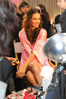 Adriana Lima sitting in a chair backstage