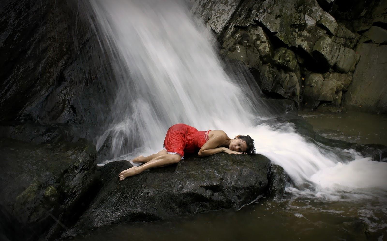 Wallpaper van een vrouw in rode jurk op de rotsen bij een waterval