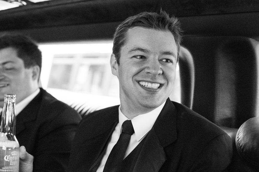 black and white candid of smiling groomsman