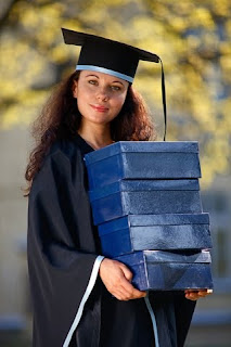 Picture of young graduate girl holding a stack of boxes.