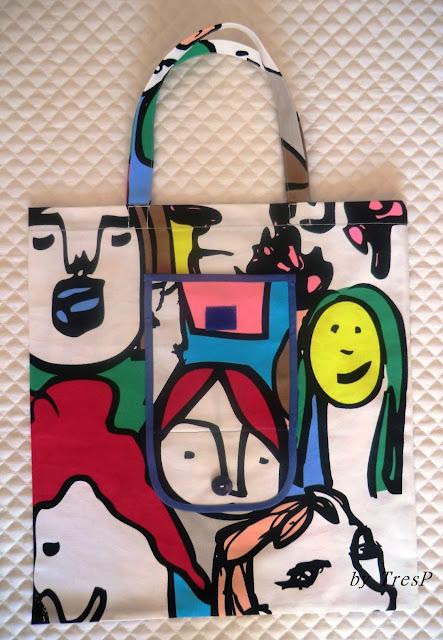 Bolsa de tela con dibujos de caras sobre fondo blanco.