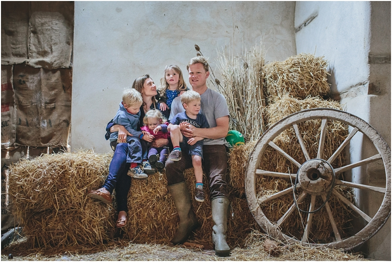A family group on hay bales in a barn