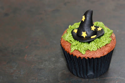 Red Velvet cupcake with buttercream grass and topped with a witch's hat