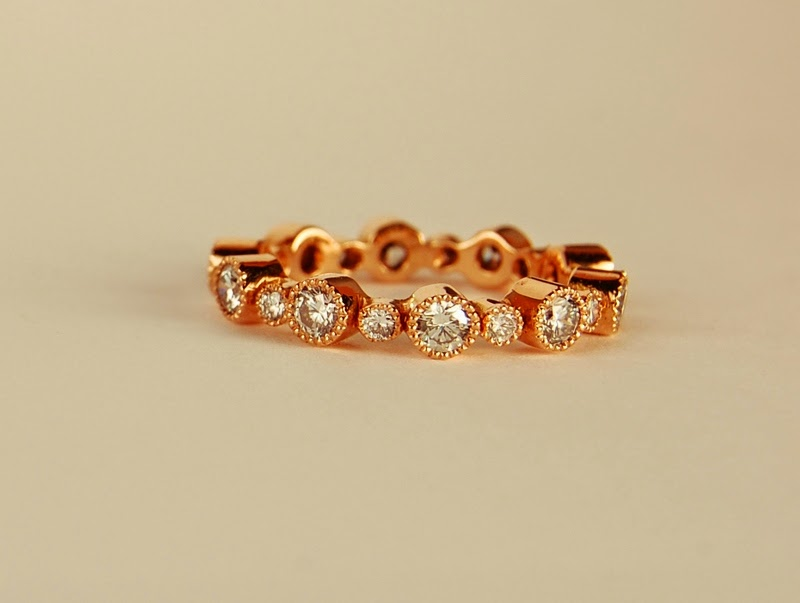 18k pink toned metal ring with large and small diamonds alternating in bezel settings with milgraine