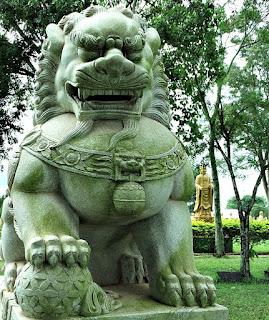 Leão de pedra sentado guarnece o Templo Budista.