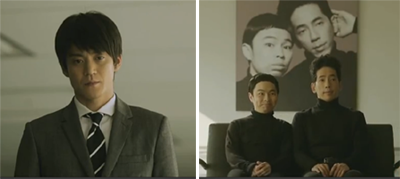 Ishikawa stares at Hacker Simon played by Hamano Kenta 浜野謙太(はまの けんた) and Hacker Garfunkel played by Nomaguchi Toru 野間口徹 (のまぐちとおる)  as they sit in front of a huge photo of themselves.