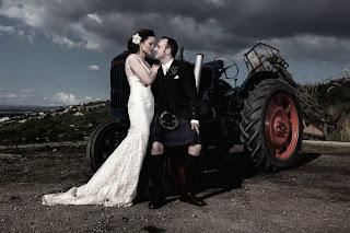 bride and groom posing beside a tractor at their wedding on bogbain farm