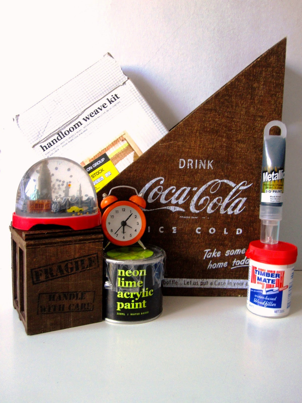 A selection of items from Typo (including a wooden Coca Cola magazine holder,a handlloom weave kit, a snow dome, tin of neon lime paint and a small orange alarm clock, Plus a small container of wood filler and a tube of  3D paint.