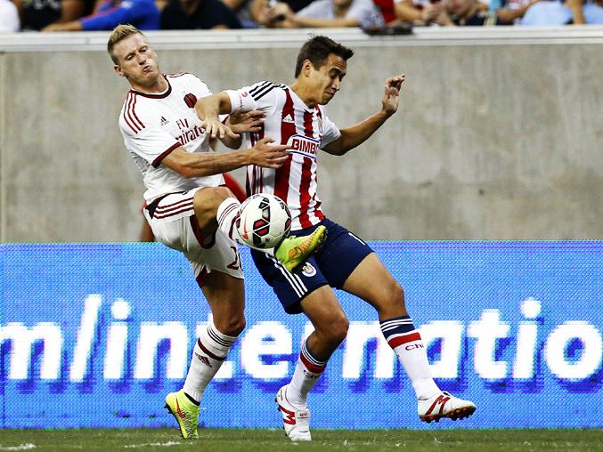 Ignazio Abate disputa un balón con Gerardo Rodríguez de Chivas.