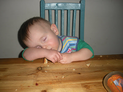 kid eating food and sleeping