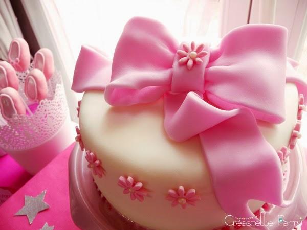 gâteau au chocolat décoré de pâte à sucre blanche et d'un gros nœud rose
