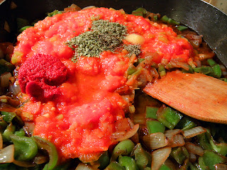 mixing togerher bell pepper, onion, tomatoes, tomato paste, herbs, salt, and pepper  in skillet