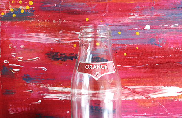 orange glass bottle on abstract painted background