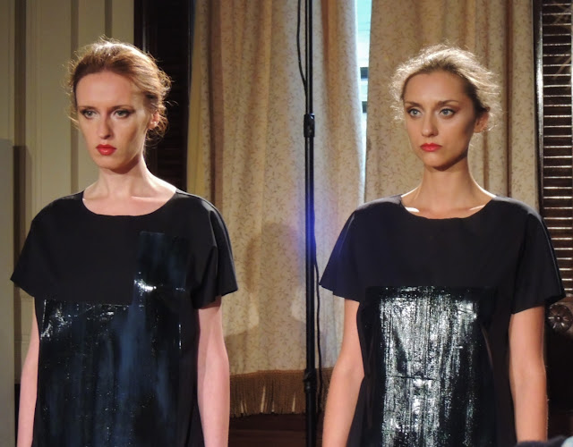 Two models in patent black dresses with chiffon