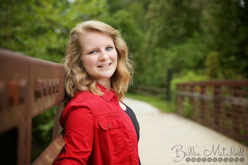 blonde teen girl in red jacket standing on metal bridge