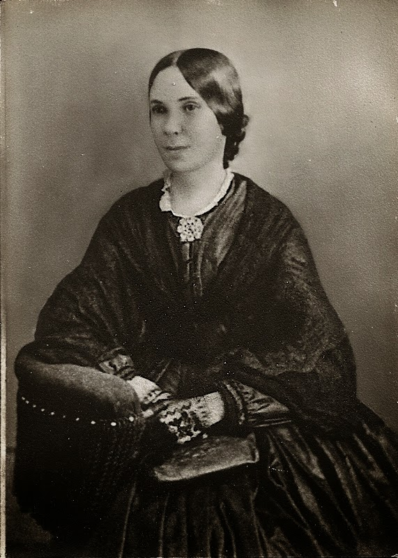 Portrait from a reproduction of a tintype of a woman, Pamelia Milburn, seated, with dark clothing of the 1860s and a shawl.