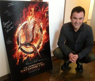 Nelson Ascencio (Flavius) beside an autographed Catching Fire movie poster.