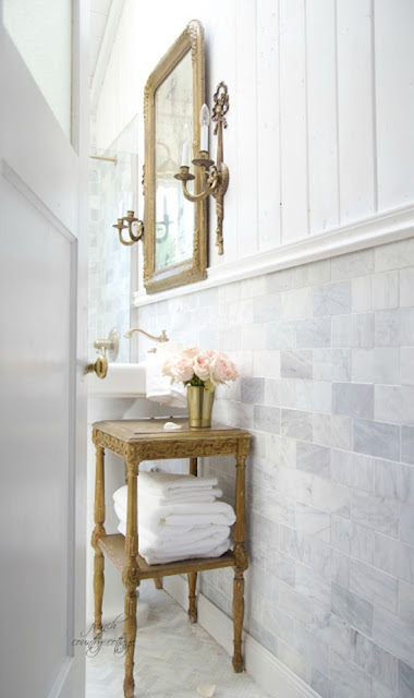 Marble subway tile and wood walls with gold mirror