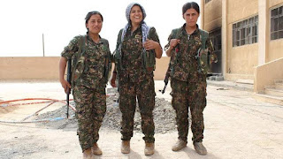 female kurdish fighter dressed in military uniform holding weapons, fighting ISIS