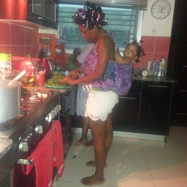 african mother annie idibia in kitchen with her baby olivia tied